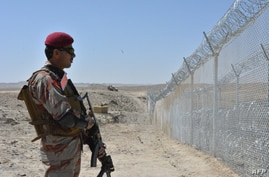 A Pakistani army soldier stands guard along with border fence at the Pak-Afghan border near the Punjpai area of Quetta in…