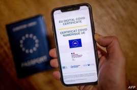 A picture taken on June 29, 2021 in Paris shows a passeport behind a mobile phone whose screen bears a EU Digital Covid…