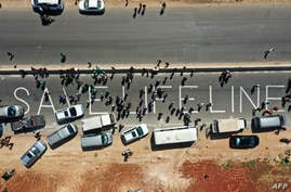 A human chain is formed by workers from the civil society, humanitarian aid, and medical and rescue services in a vigil calling…