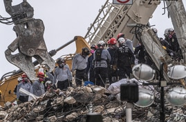 After a brief stop to demolish the standing debris, search and rescue personnel continue to work in the rain on the rubble pile…