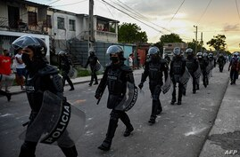Riot police walk the streets after a demonstration against the government of President Miguel Diaz-Canel in Arroyo Naranjo…