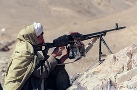 A member of Taliban, a student-led militant Islamic force aims his machine gun at the frontline in Charasyab, approximately 13…