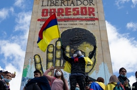 A protester waves a Colombian flag in front of a monument honoring Simon Bolivar in Bogota, Colombia, July 20, 2021. (Megan Janetsky/VOA)