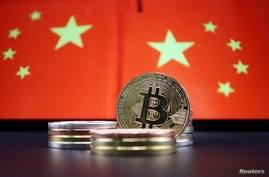 Representations of Bitcoin cryptocurrency are seen in front of an image of Chinese flags in this illustration picture taken…
