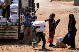 A worker holds bags and a box of humanitarian aid in the opposition-held Idlib, Syria June 9, 2021. Picture taken June 9, 2021…