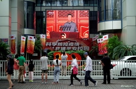 People watch a giant screen broadcasting Chinese President Xi Jinping's speech at the celebration marking the 100th founding anniversary of the Communist Party of China, in Shanghai, China, July 1, 2021.