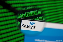 Kaseya's webpage is seen through magnifying glass in front of displayed binary code in this illustration taken, July 6, 2021…