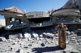 A woman gestures next to the house of jailed Palestinian assailant Muntasir Al-Shalabi, after it was blown up by Israeli forces…