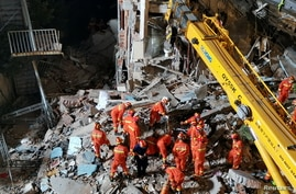 Rescue workers work next to a crane at the site where a hotel building collapsed in Suzhou, Jiangsu province, China July 12,…