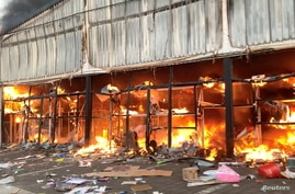 A fire engulfs Campsdrift Park, which houses Makro and China Mall, following protests that have widened into looting in…