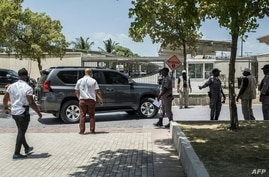 Security officers checks the surroundings of a convoy of dark-colored vehicles as it makes its way to the U.S. embassy in the Tabarre neighborhood of Port-au-Prince, Haiti, July 11, 2021.