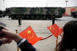 FILE - Spectators wave Chinese flags as military vehicles carrying DF-41 ballistic missiles roll during a parade to commemorate the 70th anniversary of the founding of Communist China in Beijing, Oct. 1, 2019.