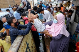 A child is handed over to board a ferry as people crowd a ferry terminal to leave the city ahead of a lockdown set to start on…