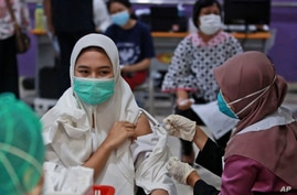 A woman receives a shot of the Sinovac vaccine for COVID-19 during a vaccination campaign at the Adam Malik Hospital in Medan.