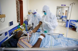 FILE — Medical staff wearing protective equipment attend to patients affected by COVID-19, on the Intensive Care Unit (ICU) of the Machakos County Level-5 hospital in Machakos, Kenya.