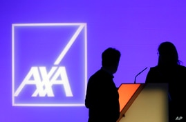 FILE - In this Feb. 21, 2019 photo, people stand in front of the logo of AXA Group prior to the company's 2018 annual results presentation, in Paris.