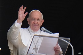 FILE - Pope Francis waves to the crowd as he arrives to recite the Angelus noon prayer.