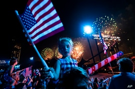 Spectators watch from the Queens borough of New York as fireworks are launched over the East River and the Empire State Building during the Macy's 4th of July Fireworks show, July 4, 2021.