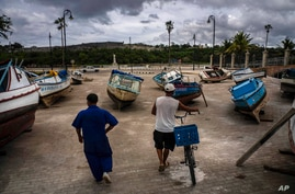 Fishermen inspect their boats after they have been taken out of the bay to avoid damage from the passage of Tropical Storm Elsa…