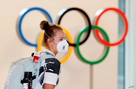 A German athlete, wearing face mask, walks past the Olympic rings display on their arrival at Haneda airport in Tokyo.