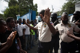 People pressure police to hand over two men who were arrested and the bodies of two men killed by police, in order to burn them in retaliation for the assassination of the President, Port-au-Prince, July 8, 2021.