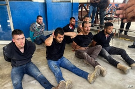 Suspects in the assassination of Haiti's President Jovenel Moise sit on the floor handcuffed after being detained.