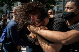 Plainclothes police detain an anti-government protester during a protest in Havana, Cuba, July 11, 2021.