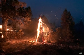 In this photo provided by the Bootleg Fire Incident Command, the Bootleg Fire burns at night near Highway 34 in southern Oregon, July 15, 2021.