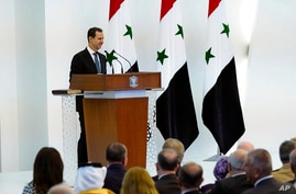 In this photo released by the official Facebook page of the Syrian Presidency, Syrian President Bashar Assad takes the oath of…