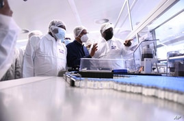 FILE - South African President Cyril Ramaphosa, right, heads a government delegation on a visit to ASPEN Pharmaceuticals in Port Elizabeth, South Africa, March 29, 2021. The company Aspen has begun production of COVID-19 vaccine for African countries.