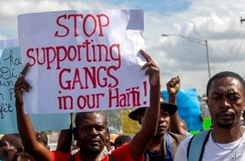FILE - A protester holds up a sign during a rally against an increase in gang violence demonstrators say the government has proven incapable of controlling, in Port-au-Prince, Haiti, Dec. 10, 2020.