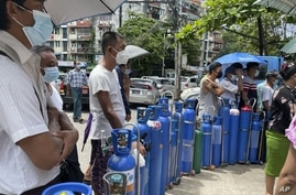 People queue with their oxygen tanks outside an oxygen refill station in Pazundaung township in Yangon, Myanmar, July 11, 2021.