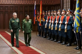Russian Defense Minister Sergei Shoigu (L) and Commander-in-Chief of Myanmar's armed forces, Senior General Min Aung Hlaing walk past the honor guard prior to their talks in Moscow, June 22, 2021.