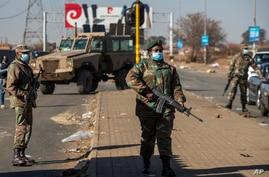 Soldiers patrol outside a shopping mall in Vosloorus, east of in Johannesburg, South Africa, July 14, 2021.
