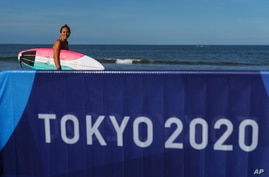 Surfer Carissa Moore, of the United States, heads into the water for a practice run at Tsurigasaki beach at the Tokyo 2020 Olympics, in Ichinomiya, Japan, July 21, 2021.