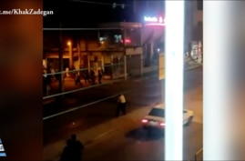In this screen grab of a video shared on social media and vetted by the Associated Press, an Iranian policeman apparently stands in the street in Susangerd after firing in the air toward protesters who run away from him on July 18, 2021.
