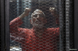 FILE - Muslim Brotherhood leader Mohamed Badie is seen behind bars during the trial of 738 brotherhood members at a court on the outskirts of Cairo, Egypt, May 31, 2016.