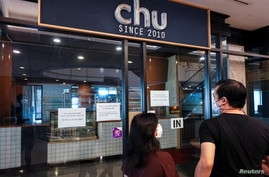 People look inside Chu Chocolate Bar & Cafe days after it permanently closed due to business lost as a result of coronavirus restrictions, in Bangkok, Thailand, June 1, 2021.