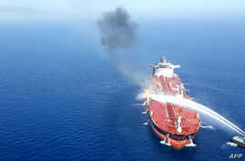 An Iranian navy boat tries to stop the fire on an oil tanker after it was attacked in the Gulf of Oman, June 13, 2019.