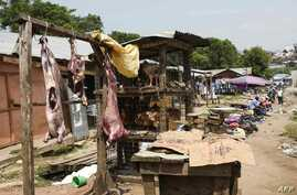 People sit and go about their daily life at the food market in Mpondwe by the border check point, between Uganda and the Democratic Republic of Congo, on June 13, 2019