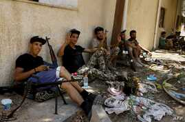 Fighters loyal to the internationally-recognized Libyan Government of National Accord (GNA) take a rest near their weapons in the al-Sawani area during clashes with forces loyal to Libya strongman Khalifa Haftar, June 19, 2019.