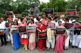 Members of the parliament (MP) from Samajwadi Party (SP), Dravida Munnetra Kazhagam (DMK) and Trinamool Congress (TMC) parties display placards during a protest calling for action in a rape case in Uttar Pradesh, at the  Parliament House in New…