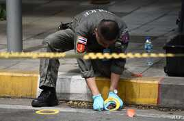 A policeman conducts an investigation at the scene of an explosion in Bangkok, Aug. 2, 2019. At least two small explosions hit Bangkok, police said, as the country hosts a regional summit attended by U.S. Secretary of State Mike Pompeo.