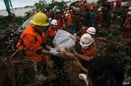 Rescue workers carry the body of a landslide victim in Paung township, Mon state, Aug. 10, 2019. The death toll from a landslide triggered by monsoon rains in eastern Myanmar rose to nearly 50.