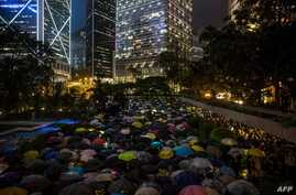 People from the finance community hold umbrellas and shine lights during a protest against a controversial extradition bill in Hong Kong, Aug. 1, 2019. Hundreds of financial workers braved pouring rain, giving that sector's support to protests that have roiled the territory for weeks