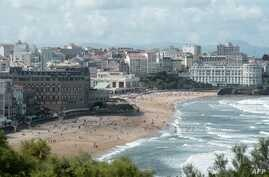 People swim in the sea and walk on the beach in Biarritz, on Aug. 13, 2019.