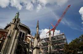 A picture taken on August 19, 2019 shows a crane at the cathedral of Notre-Dame of Paris worksite, as works to restore the cathedral following a devastating fire in April resumed, after lead scare. French workers on August 19 resumed efforts to…