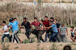 TOPSHOT - Palestinian protesters carry away a man injured during clashes following a demonstration along the border with Israel east of Bureij in the central Gaza Strip on September 6, 2019. Two Palestinian teenagers were killed by Israeli fire in…