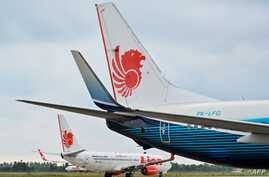 (FILES) In this file photo taken on September 3, 2019 a Lion Air Boeing 737-800 aircraft is seen at the airport in Padang, West Sumatra.   Boeing has reached settlements with 11 families of victims from October's Lion Air crash, the first agreements…
