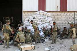 Turkish soldiers and Turkish-backed Syrian rebels gather near the Syrian border town of Ras al-Ain on October 12, 2019, as…
